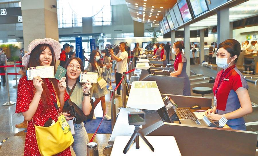 國籍航空公司成功推出各式類出國行程,日本、澳洲、新加坡等國家跟進。圖為松山機場舉辦類出國活動,民眾在機場櫃檯報到,領取登機證後開心展示登機證,過過出國乾癮。(本報資料照片)