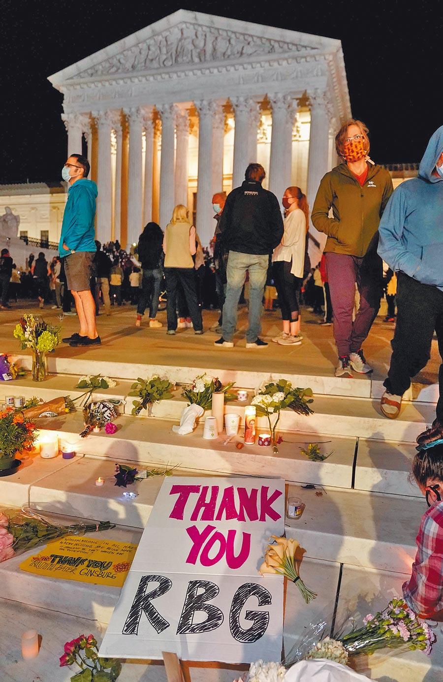 美國聯邦最高法院大法官金斯柏格(Ruth Bader Ginsburg)癌症逝世後,民眾18日在華府最高法院前方階梯,放上表示感謝與哀悼之意的鮮花與海報。(路透)