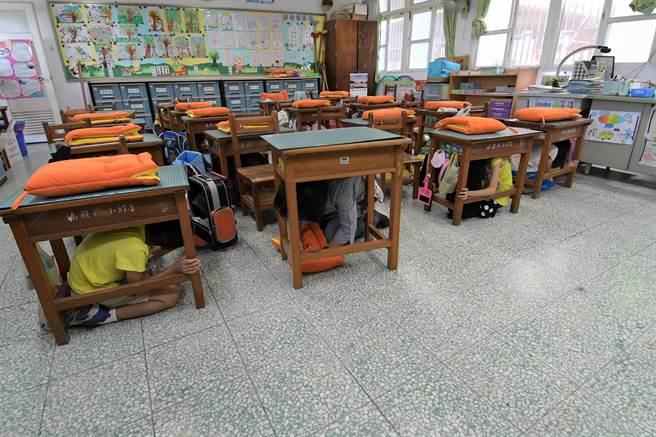 王惠美與小朋友一同躲在桌子底下,她說觀察小朋友的演練,發現他們的警覺性相當高。(吳建輝攝)