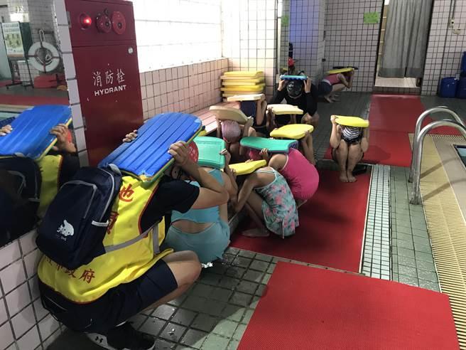 基隆碇內國小加強水域避難情形,學生在泳池上課聽到警報時,必須切記「迅速上岸、蹲下靠牆、浮板護頭」。(陳彩玲攝)