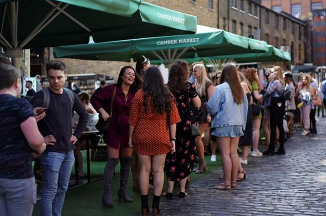 新冠疫情在英國似有捲土重來之勢,但在倫敦,年輕人很少戴口罩,也照樣群聚,沒把疫情當回事。(路透)