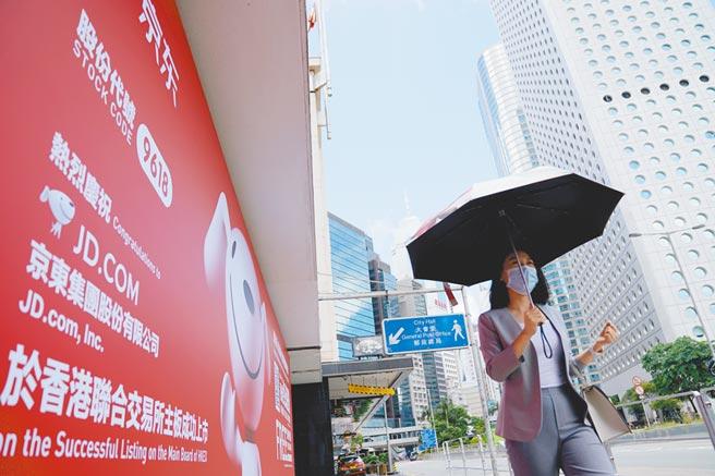 6月18日,京東集團在港交所掛牌上市。圖為行人從中環一處京東在香港掛牌上市的廣告前走過。 (新華社)