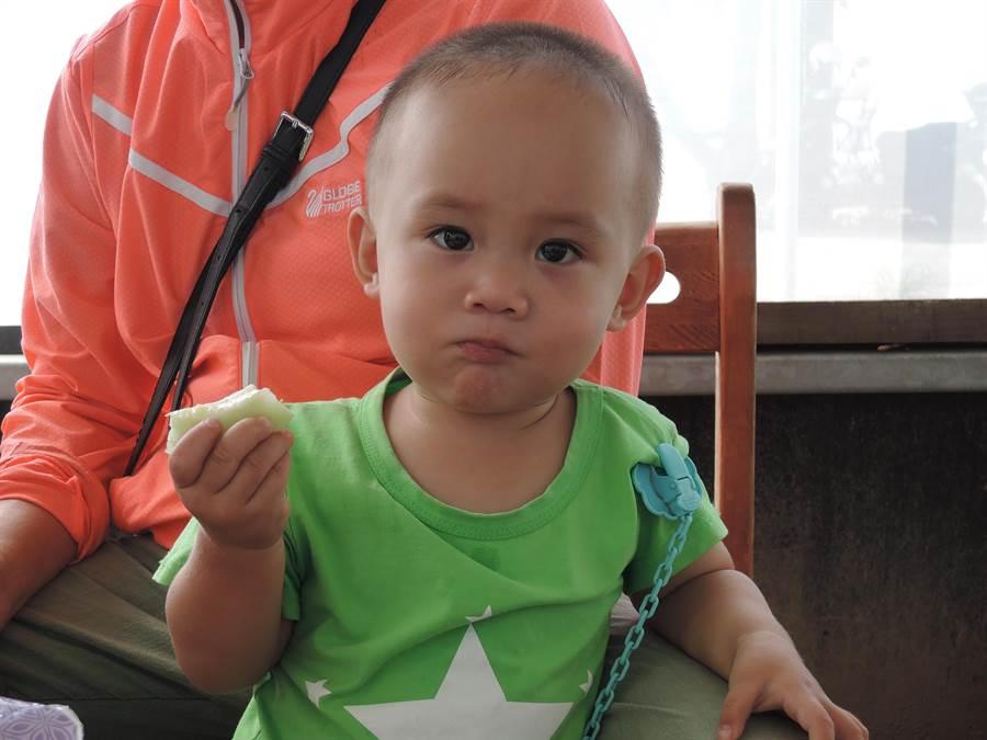 郭德杉的兒子津津有味吃著「嘉玉」美濃瓜。(張毓翎攝)