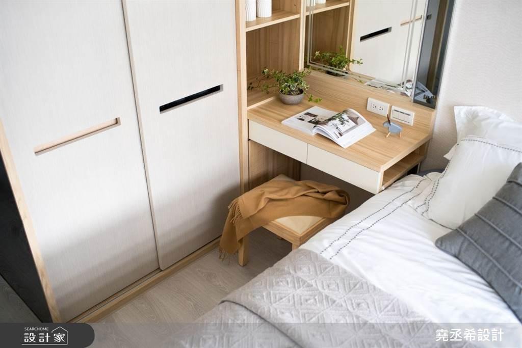 系統櫃於臥房的運用層面也很多元,除了常見的衣櫃收納之外,還能根據空間訂製床邊的化妝台或床頭櫃,整合性極高。(圖片提供/堯丞希設計)