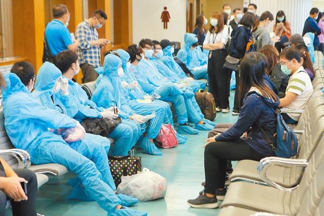 289名越南移工在21日由移民官一对一戒护,所有移工都两两用手铐铐在一起,直到登机前才解铐。(陈麒全摄)