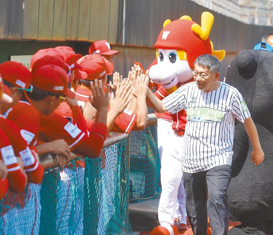 全台唯一人工草皮的天母棒球場昨舉行完工啟用紀念賽,台北市長柯文哲(右)開球後與味全龍選手擊掌。(陳怡誠攝)