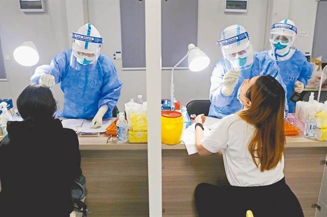 在上海浦東機場,工作人員對入境旅客進行核酸檢測。(中新社)