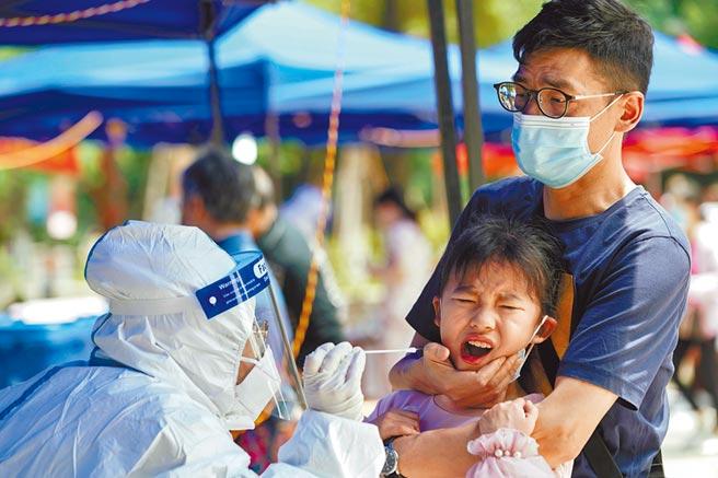 在湖北省武漢市,一名兒童在接受核酸測試時有反應,該市是新冠病毒疫情最嚴重的大陸城市。美國眾議院共和黨領袖公布疫情最終報告,譴責大陸隱匿疫情。(路透)