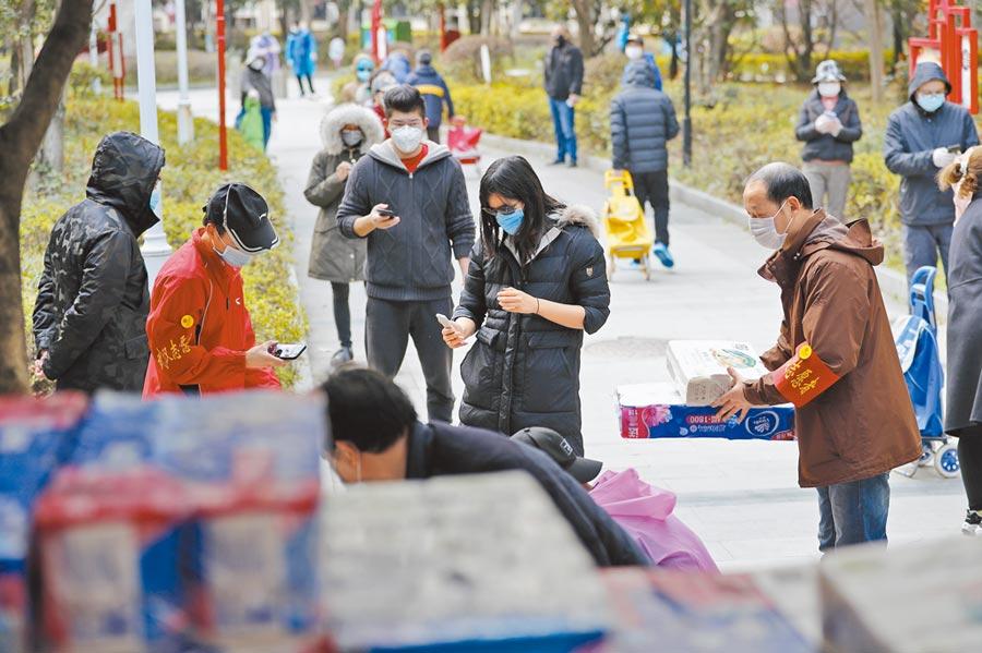 2月24日,武漢市江岸區百步亭社區龍庭小區的居民,排隊購買團購的生活必需品。(新華社)