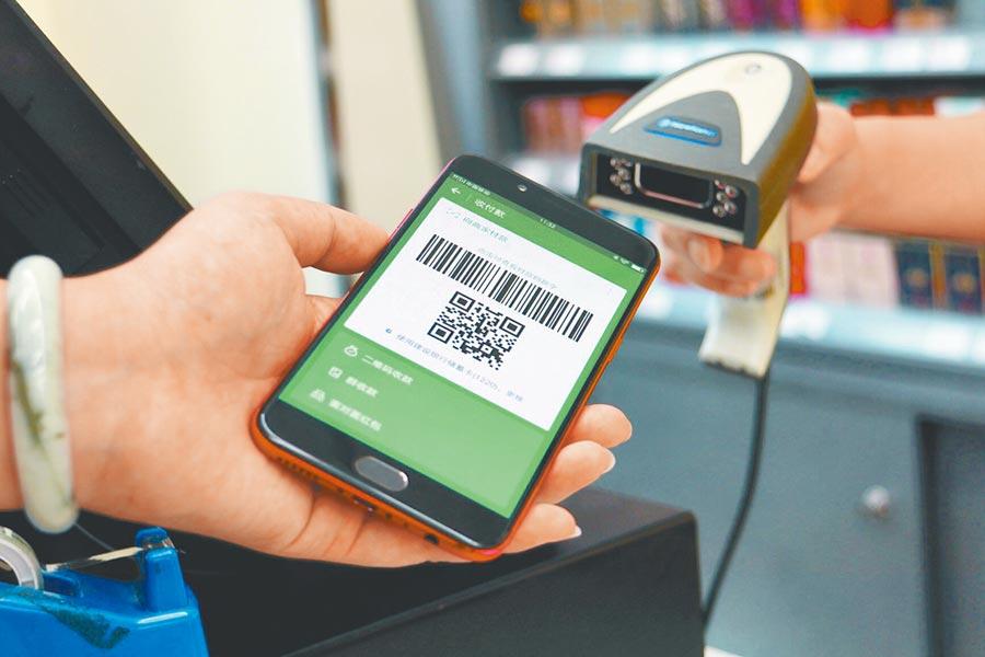 大陸將加速數位貨幣落地,進入無現金社會。圖為成都民眾使用手機二維碼支付。(中新社資料照片)