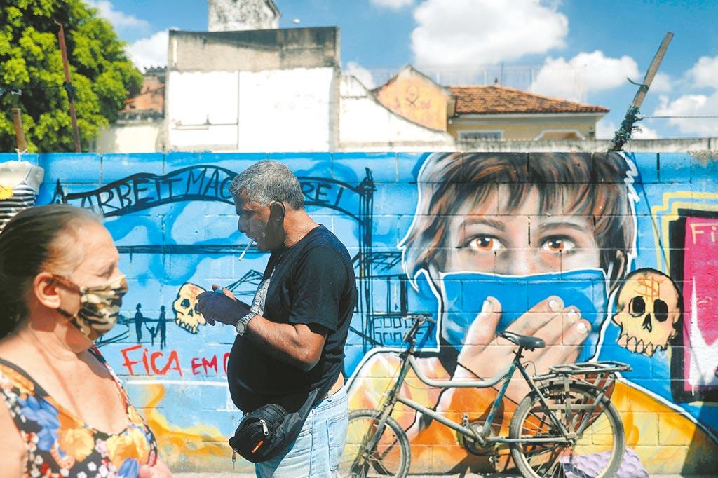 外國疫情延燒,圖為巴西里約熱內盧,塗鴉牆的人物戴著大口罩。(路透)
