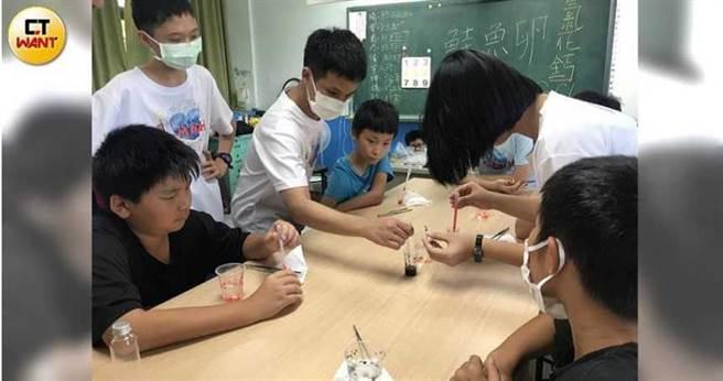 科普社的社員們分成許多組,合作指導每桌小朋友動手做實驗。(圖/讀者提供)