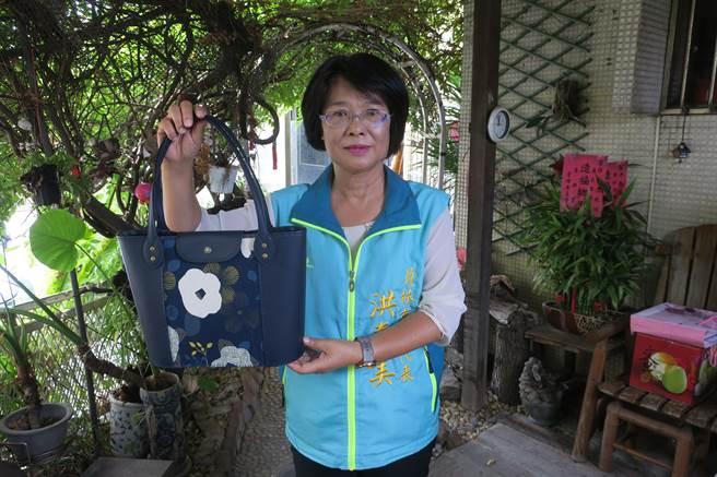 洪春美手上的藍色手提包包,是最近里長才藝教室婆婆媽媽們的成果作品。(謝瓊雲攝)