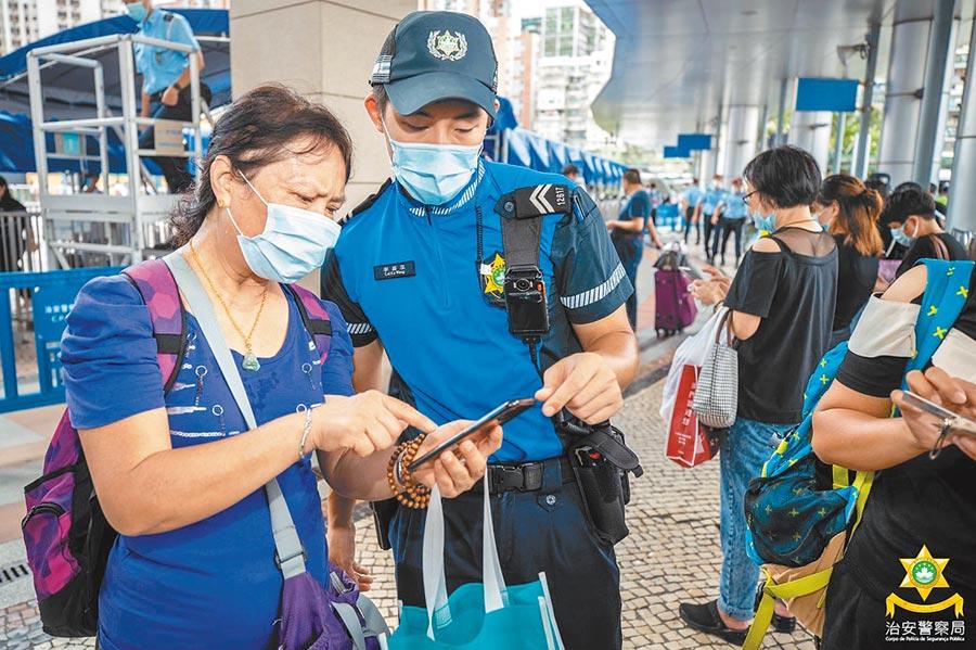 澳門旅遊警察在指導民眾轉換粵澳兩地的「健康碼」,以利快速通關。(中新社資料照片)
