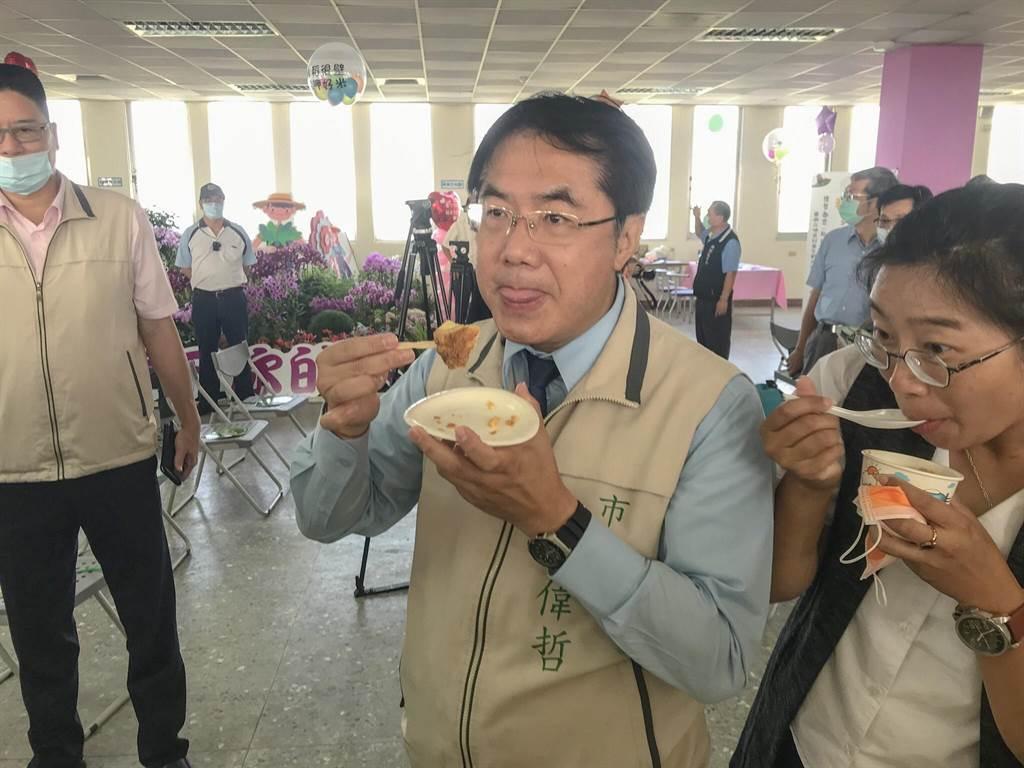 台南市長黃偉哲見美食當前,不顧鏡頭大口吃下米布丁。(周書聖攝)