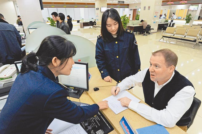 2019年11月29日,浙江義烏市國際貿易服務中心辦事大廳,工作人員在為外商提供諮詢服務。(新華社)
