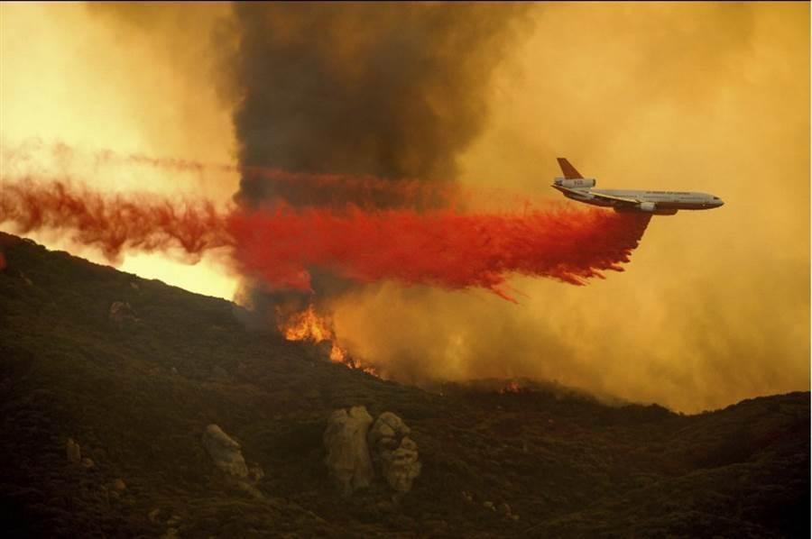 美國加州野火肆虐,一架DC-10空中加油機投下了阻燃劑,以減緩大火燃燒。(美聯社)