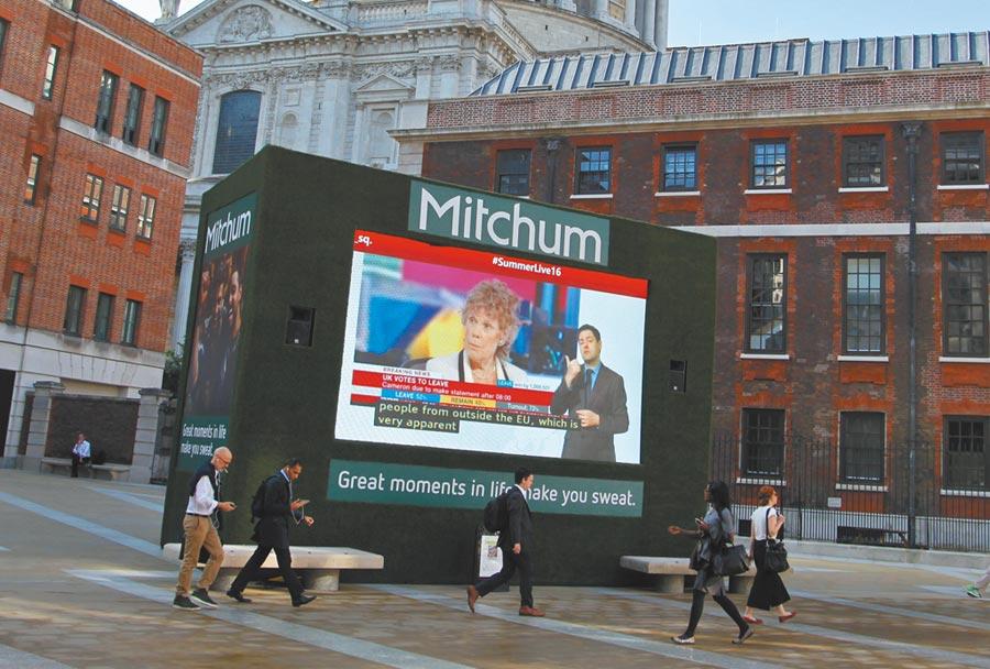大陸國債有望納富時指數。圖為人們走過倫敦證券交易所門前廣場上的大螢幕。(中新社)