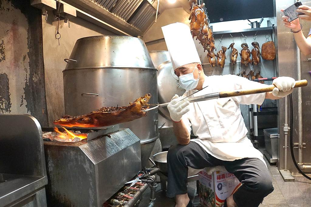 好吃的〈化皮乳豬〉必須靠人工以直火炭烤,操作過程很費力。(圖/姚舜)