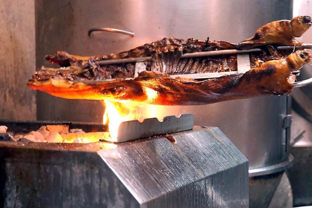〈脆皮乳豬〉要達到「化皮」效果,除火要旺且要均勻受熱,同時燒烤過程要不斷反覆塗油,利用「油爆」使豬皮鬆化。(圖/姚舜)