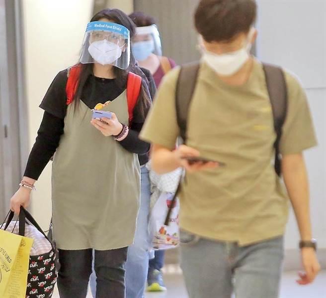 駐法國代表處二名職員確診「新冠肺炎」(COVID-19)。圖為一群旅客11日搭機抵達桃園機場,準備通關入境。(范揚光攝)