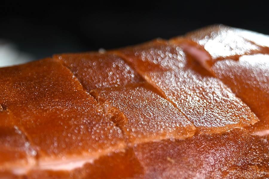 近距離細看利用「油爆」效果燒烤的〈化皮乳豬〉,酥皮上有微粒凸起。(圖/姚舜)