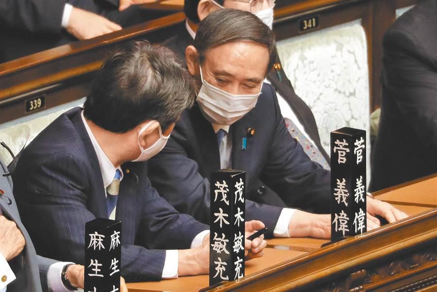 菅義偉(右)與獲留任的外務大臣茂木敏充交換意見。(新華社資料照片)