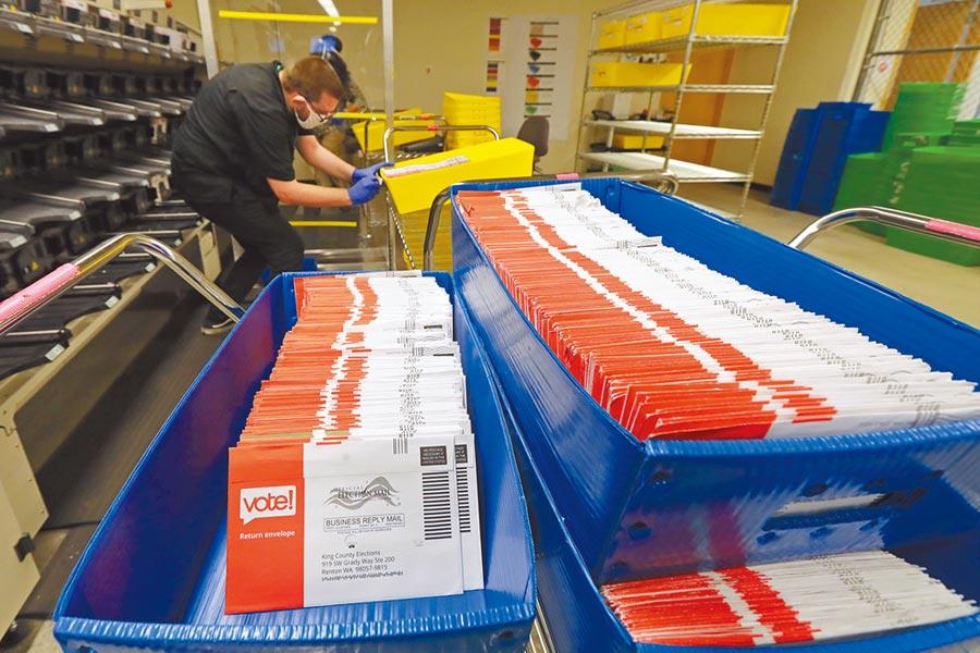 美國華盛頓州國王郡選舉總部,工作人員正在將收到的郵寄選票擺放進托盤。受到新冠疫情影響,今年美國大選採用郵寄投票的美國選民大幅增加。(美聯社)