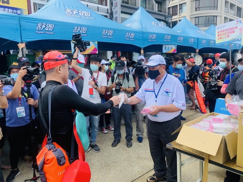 南投縣副縣長陳正昇(右),發送口罩給上岸泳客。(廖志晃攝)