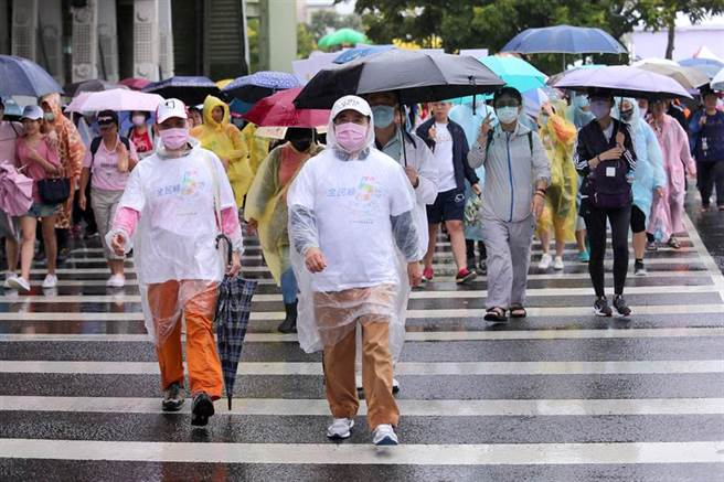 前立法院長、台灣癌症基金會董事長王金平(中)穿著雨衣和上千位民眾在雨中健走。(黃世麒攝)