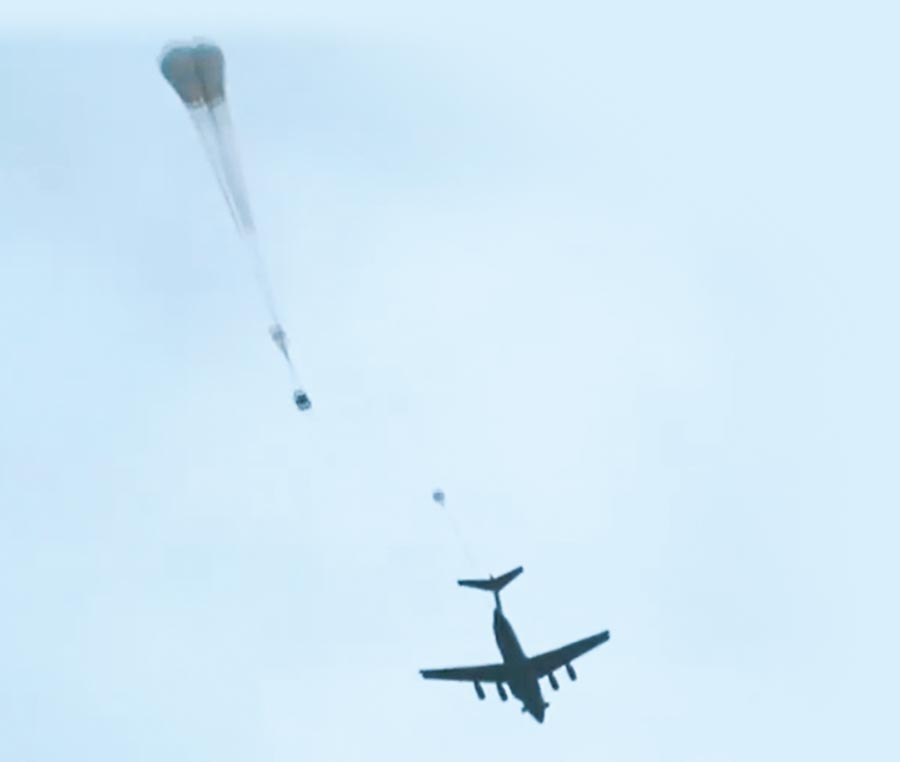 8月底,運-20運輸機在高原空投大型裝備,牽引傘被拋出後綻放傘花。(取自微博@央視軍事)