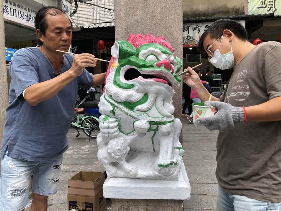 金門陶藝工作者王明宗(左)替邱良功母節孝坊的石獅彩繪換妝,引來中央文資單位的關注。(李金生攝)