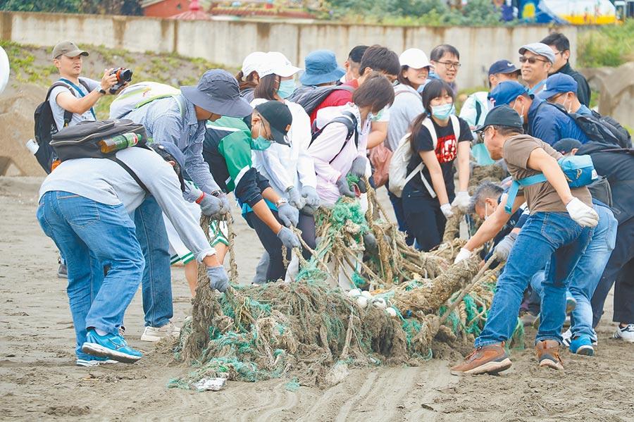 愛護海洋、守護地球,國泰證券、國泰期貨一起行動淨灘活動團結力量大,同仁們一同清理海灘上重達百斤的漁網。圖/國泰證券提供