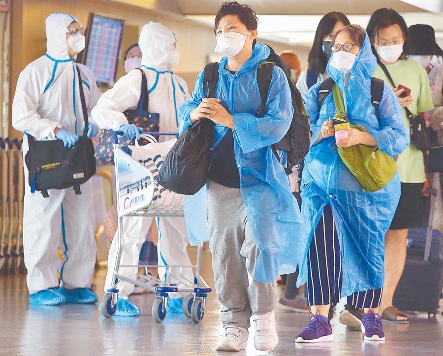 一群搭機抵達桃園機場的旅客,在入境前準備查驗健康聲明書。(范揚光攝)