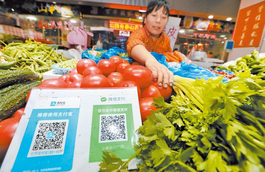 江蘇南通一家菜市場,攤販把支付寶、微信支付的二維碼擺在醒目位置。(新華社資料照片)