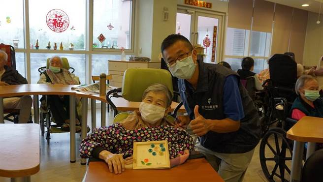 元大人壽志工陪同老奶奶完成手作紙捲花。(圖/元大人壽提供)