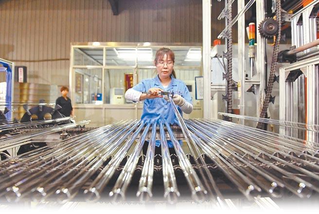 工人在河北滄縣一玻璃生產廠內檢驗玻璃管品質。(新華社資料照片)