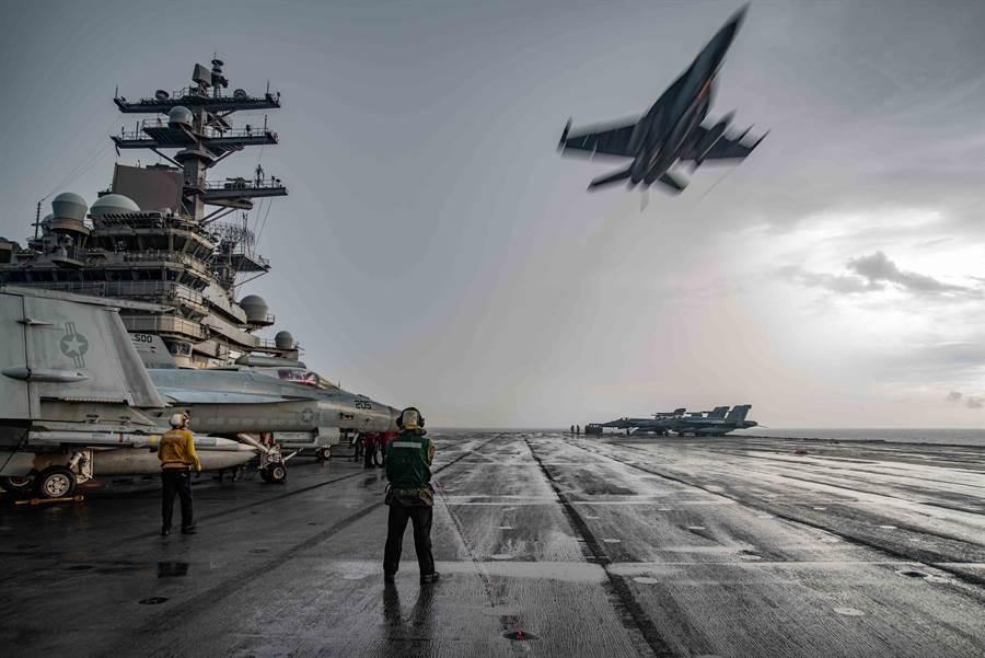「雷根」號航母4日在南海軍演,圖為一架F/A-18E「超級大黃蜂」(Super Hornet)戰機飛越甲板的畫面。(美國海軍)
