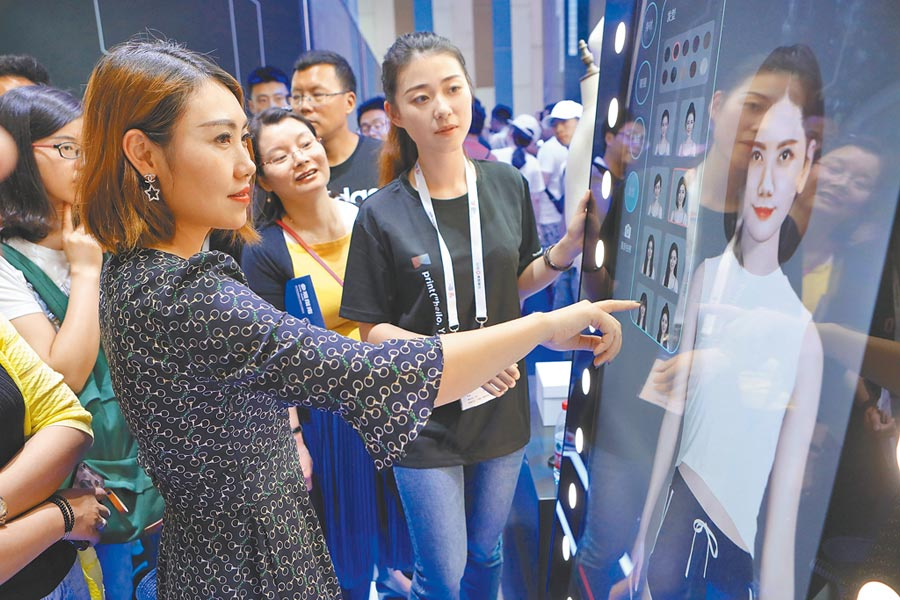 大陸的虛擬經濟,服務範圍廣。圖為貴陽大數據博覽會,民眾透過阿里的虛擬試衣鏡試衣。(新華社)