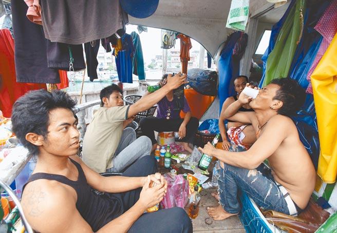 近日傳出我國漁業被列入美國「童工及強迫勞動製品清單」,對此國內漁會表示,這是對台灣的漁業警告。圖為宜蘭縣蘇澳鎮南方澳第1漁港的印尼漁工聚在船上喝酒聊天。(本報資料照片)(飲酒過量,有害健康)
