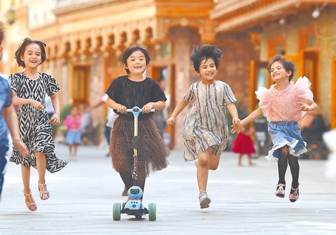 文化潤疆的提出被認為是懷柔少數民族。圖為新疆少數民族孩童在街上玩耍。(新華社資料照片)