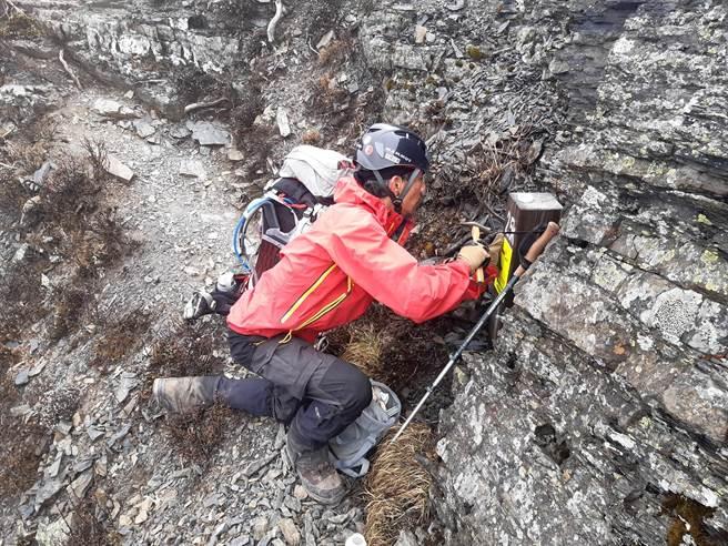 工作人員於聖稜線2.5K里程樁上設置手機可通訊處牌面。(雪管處提供/巫靜婷苗栗傳真)