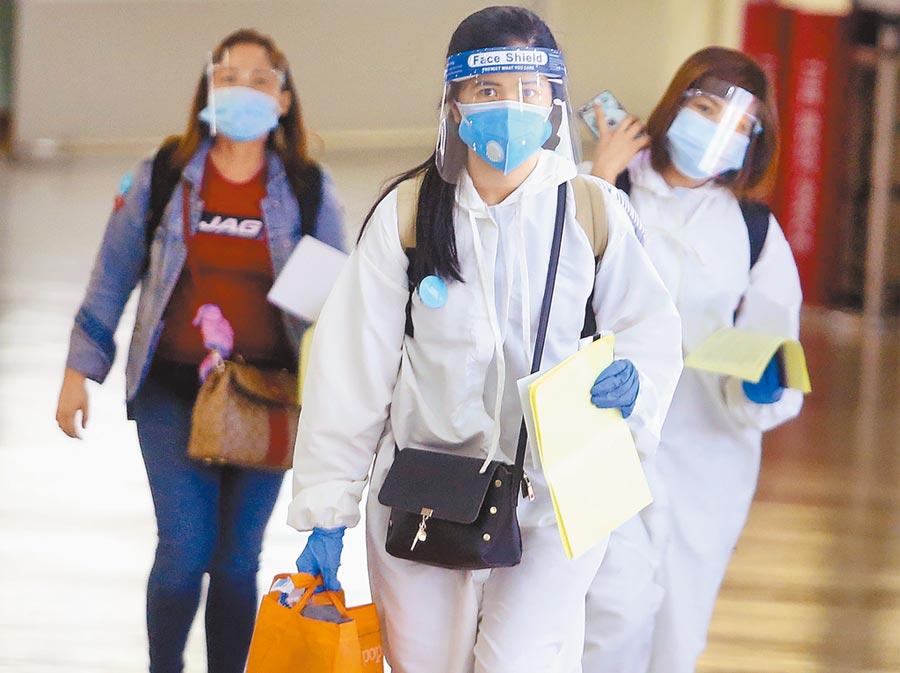 示意圖。圖為3名搭機抵達桃園機場的旅客,入境前準備查驗健康聲明書。(資料照/范揚光攝)