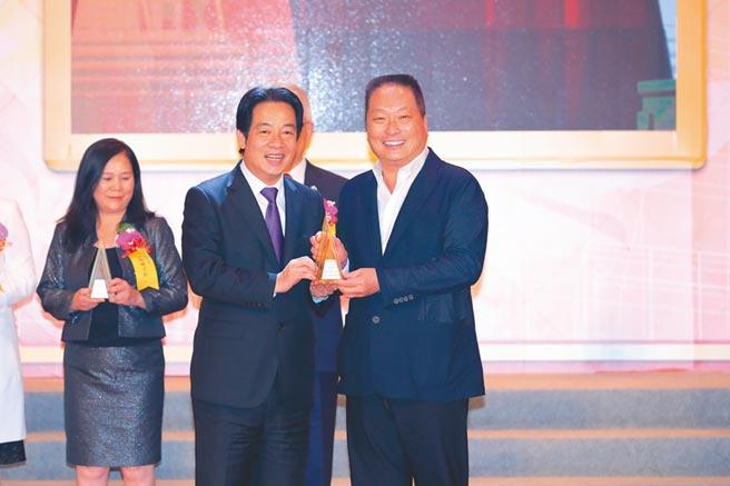 東森自然美榮獲「國家品牌玉山獎」傑出企業獎、傑出產品獎,東森集團總裁王令麟(右)親自出席,自副總統賴清德(左)手中領取獎座。圖/東森提供