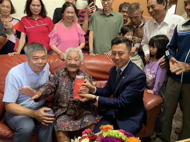 新竹市長林智堅今天特別轉送總統府敬老狀及衛生福利部金鎖片予張林寶老奶奶。(陳育賢攝)
