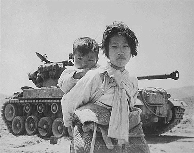 中共參加韓戰動員240萬人,死亡人數高達20萬人,美軍與南韓也傷亡慘重。圖為韓戰時期美軍坦克與南韓姐弟的一張知名的戰地攝影。(圖/公開檔案)