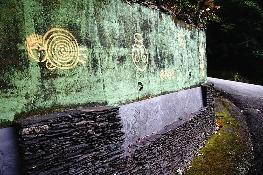 進入萬山部落,由馬樂創作的萬山岩雕引道連綿數百公尺。(圖/曾信耀攝)