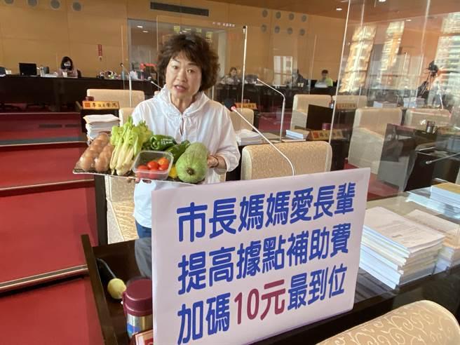 市議員李麗華16日在民政質詢時,端出一盤菜,包括絲瓜、白菜、蕃茄等,還有一盒蛋,爭取加碼10元補助。(盧金足攝)
