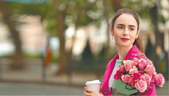 美劇《艾蜜莉在巴黎》女主角莉莉柯林斯在劇中身穿KENZO桃紅色羊毛大衣,並在巴黎街頭買花認識新朋友卡蜜兒。(Netflix提供)