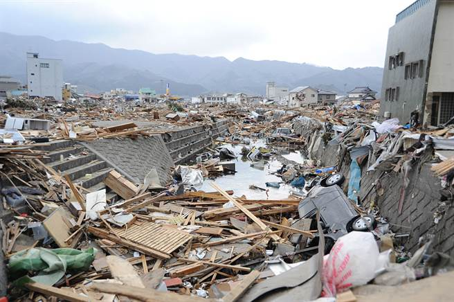 圖為2011年311大地震,日本岩手縣大船渡市被巨大海嘯破壞的房屋和汽車。(圖/摘自維基百科)